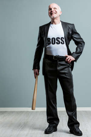 mobbing: Happy mature supervisor standing alone while holding one wooden baseball bat over gray background Stock Photo