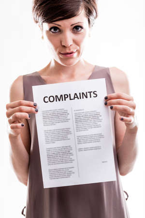 front facing: Thoughtful woman standing facing the camera holding a printed list of complaints in front of her , cropped upper body close up view