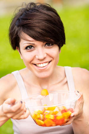 Single beautiful woman with big smile eating fruit from clear plastic bowl with fork outdoors