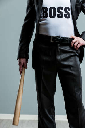 Business Boss concept with a businessman in a suit wearing a Boss t-shirt standing with one hand on his hip holding a baseball bat in a close up body view