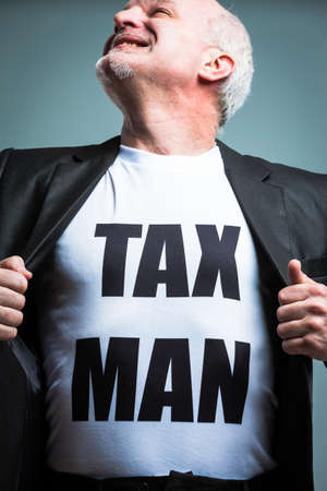 heroic: Happy mature bearded man looking upward in heroic pose while opening suit jacket with tax man text in large letters on torso.
