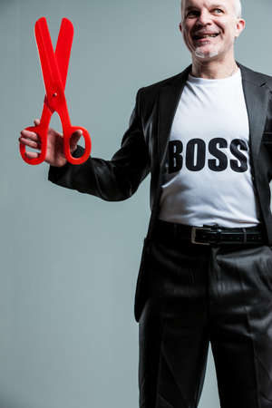 Happy mature boss man with large red scissors over gray background for concept about bureaucracy or intimidation