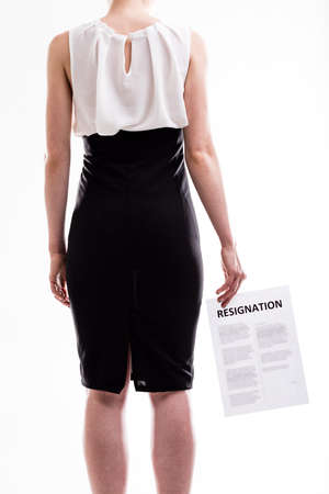 resignation: Woman in a formal black skirt standing with her back to the camera holding a resignation letter, torso view isolated on white