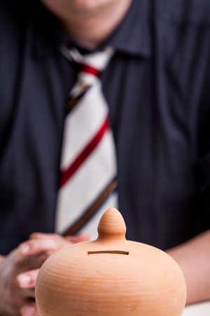 Krawatte eines Büroangestellten, Geschäftsführer oder Manager eines Sparbüchse Beobachtung der Notwendigkeit darstellt, um Geld zu sparen