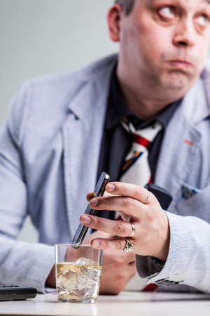 frustrating: stressed manager putting his smartphon on alcohol because of his frustrating wait on the phone Stock Photo