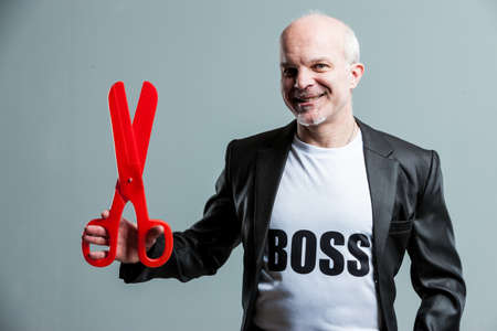 sadistic: Smiling senior businessman wearing a Boss t-shirt holding up a large pair of red plastic scissors in his hand with a smile in a conceptual image Stock Photo