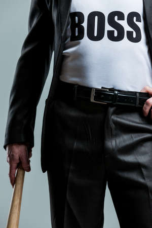 sadistic: Cropped view of business man gripping his pants belt and holding wooden bat in other hand with boss text on shirt