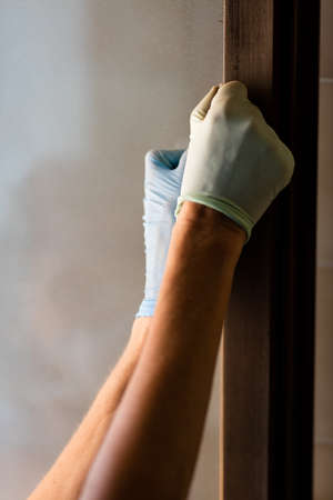redecoration: Close up on thin rubber gloved hands sanding or painting side of door inside room with copy space