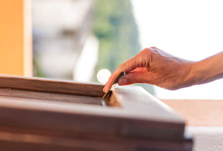 sandpaper: Hands of a woman with sandpaper doing DIY work on wooden fixtures Stock Photo