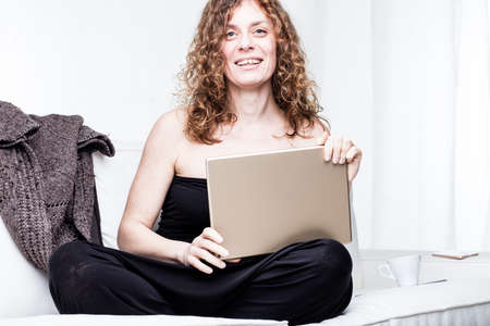 sleeveless top: Single smiling pretty woman in sleeveless top holding large tablet computer while sitting cross legged on sofa with sweater beside her in bright white room