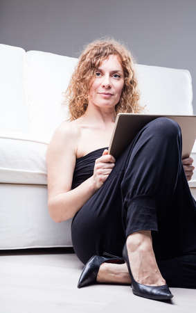 sleeveless top: Single middle aged woman in dark sleeveless top and high heels with frame or tablet in hand