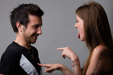 provoke: woman picking on his boyfriend joking and laughing at him while handling with fingers on his chest Stock Photo