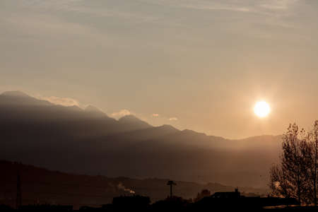 unedited: wallpaper or background of northern Italy sunrise in the mountain with little town skyline in silohouette