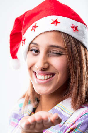 Fun vivacious woman wearing a festive red Santa hat winking at the camera with a broad grin as she celebrates Christmas Stock Photo