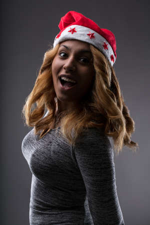 afro-american pretty woman with a Santas Hat expressing shock with her mouth shouting ooh and wishing you a merry Cristmas