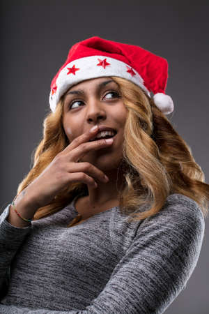 leer: flirting girl thinking about a gift for Christmas on a Santa Claus hat