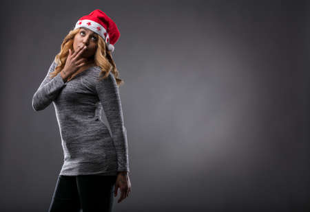 flirting girl thinking about a gift for Christmas on a Santa Claus hat