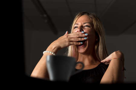 Tired woman working late at night on a laptop computer yawning with her hand to her mouth by the light of the screen, low angle view past a cup of coffee