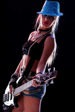 sensual girl playing on stage on a dark background as a popstar or rockstar Stock Photo