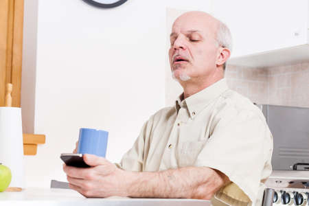 mature man has problems with his eyesight and struggles reading on his smart phone Stock Photo