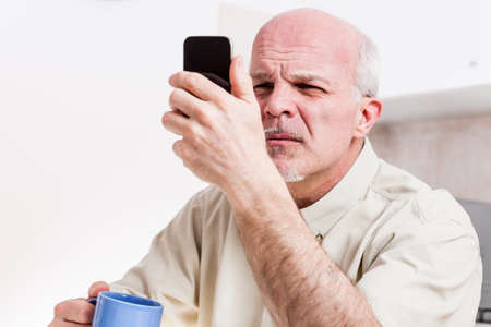 senior man has problems with his vision while trying to read or watch something on the screen of his mobile phone in his kitchen