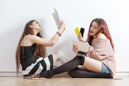 a girl sat intent on reading her book in front of another girl using a digital tablet and 4 mobile phones listening, reading and whatever