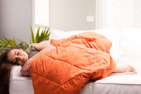 woman sleeping like a baby in her very comfortable living room on her white sofa under an orange quilt Stock Photo