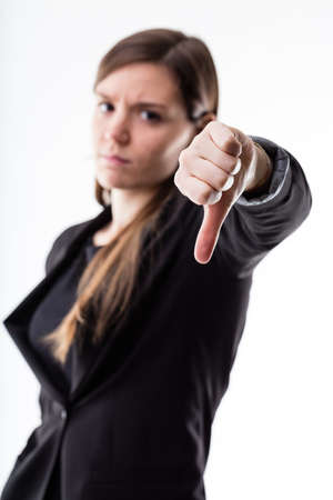 expressing negativity: thumb down in focus by a woman in blurred background expressing NO