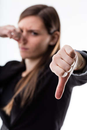 blame: thumb down in focus by a woman in blurred background pinching her nose and expressing disgust and blame for something dirty or wrong