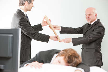 manager passes a bat to the boss to beat a lazy employee surprised to sleep on his desk instead of working