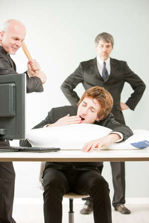 violence in the workplace: mature boss about to hit with  baseball bat a lazy employee caught yawning while he sleeps on the job while a manager follows and approves