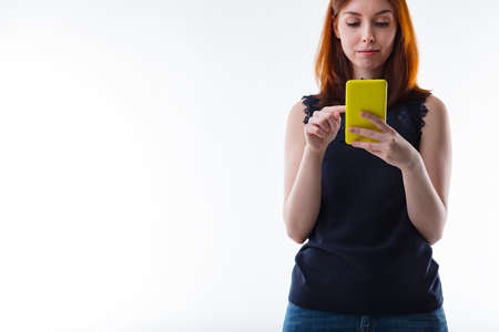 alongside: woman texting with her mobile phone alongside wide white copyspace Stock Photo