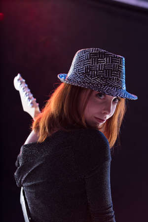 guitar player turning her head to look you while playing her guitar Stock Photo