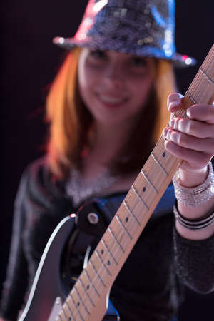buisness woman: focus on the left hand on the guitar grip by a popstar playing her musical instrument onstage, her face is blurred in the background but shes smiling