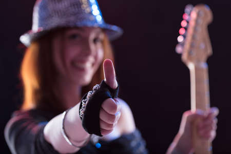 buisness woman: focus on thumbs up by a popstar guitar player on stage, while smiling to you during her show