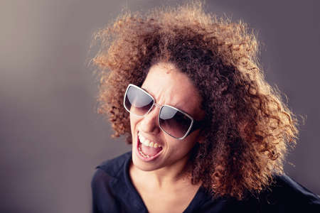 portrait of a curly haired inspired young woman singing or shouting loud with her mouth wide open Stock Photo