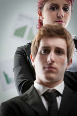 disregard: concept of a woman bullying a man on the workplace by controlling him strictly and hopelessly Stock Photo