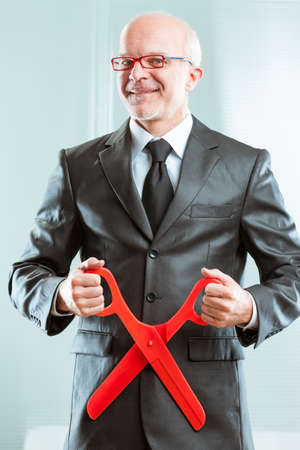 grotesque sadistic accountant ready to cuts with giant red scissors