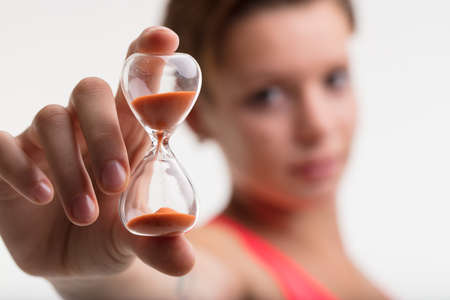 urging: young woman urging you to complete you daily workout by showing you a hourglass, meaning that time goes by