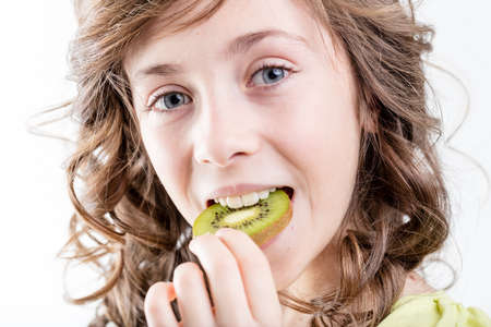 close up portrait of a girl putting a kiwi slice in her mouth shes about to bite and eat because she enjoys the flavour and she knows this is very healthy because of the vitamins Stock Photo