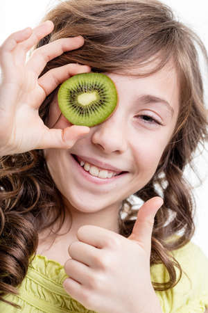 smiling girl portrait as she covers her eye with a kiwi slice as showing thumb up for vitamins