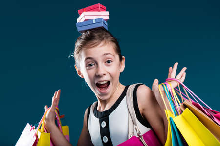 OMG shopping online and offline is SO funny says this little girl covered with packets and colorful shopping bags