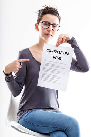amiable: friendly office worker pointing out a resume (curriculum vitae)  meaning you can submit your application form and be hired Stock Photo