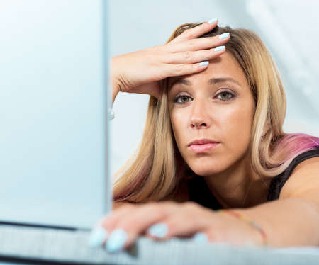 sleepiness: tired woman with her hand on her brow as she read something on her computer screen even if shed better go to sleep
