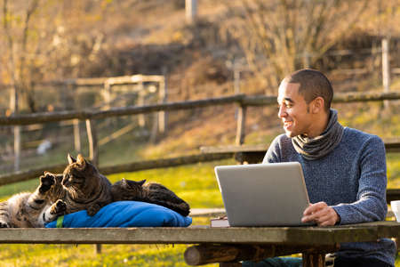 fine business young man working outdoor at his notebook smiling at three cats playing and sleeping