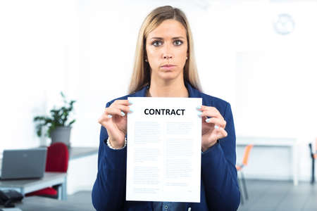 stern: stern and blank business woman holding a contract with both hands in a workplace Stock Photo