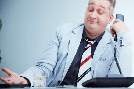 emphasized: service operator at the phone expressing his total indifference for customers problems Stock Photo