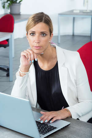 young woman in her office workplace looking to you as she uses her laptop  personal computer