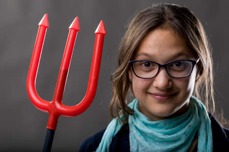 devilish: portrait of a little rascal girl with a red pitchfork meaning she is a little devil ready to make some pranks and jokes to have some fun Stock Photo