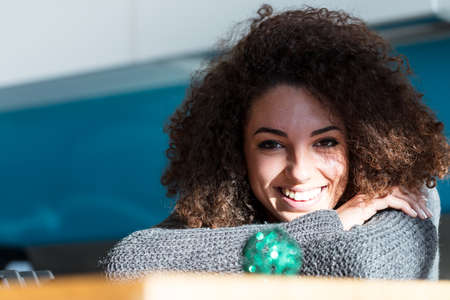 afroamerican: cute young woman with curly hair smiling next to a green christmas ball (blurred in foreground) in her kitchen Stock Photo